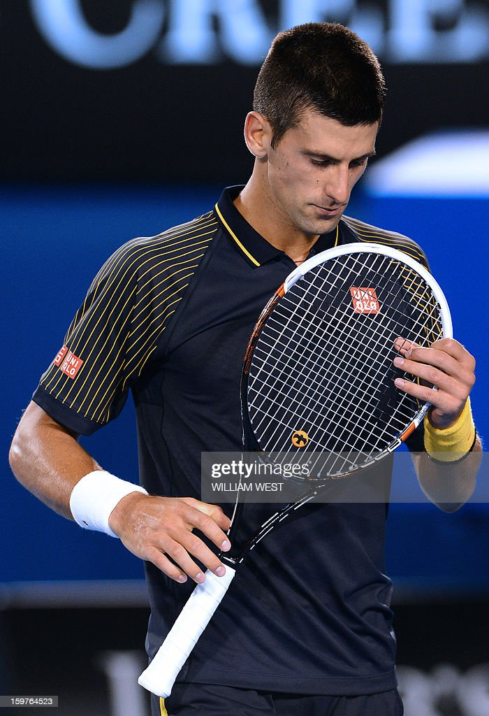 Serbia's Novak Djokovic examines his racquet during his men's singles match against Switzerland's Stanislas Wawrinka on the seventh day of the Australian Open tennis tournament in Melbourne early January 21, 2013.