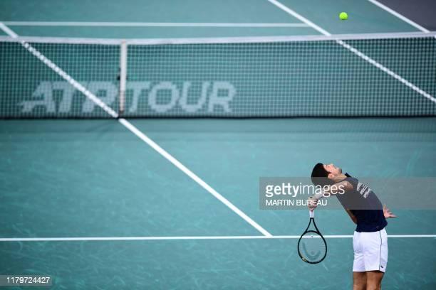 Serbia's Novak Djokovic eyes the ball as he serves to Canada's Denis Shapovalov during their men's singles final tennis match at the ATP World Tour...