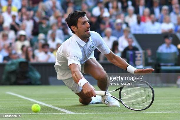Serbia's Novak Djokovic falls reaching for a return against US player Denis Kudla during their men's singles second round match on the third day of...