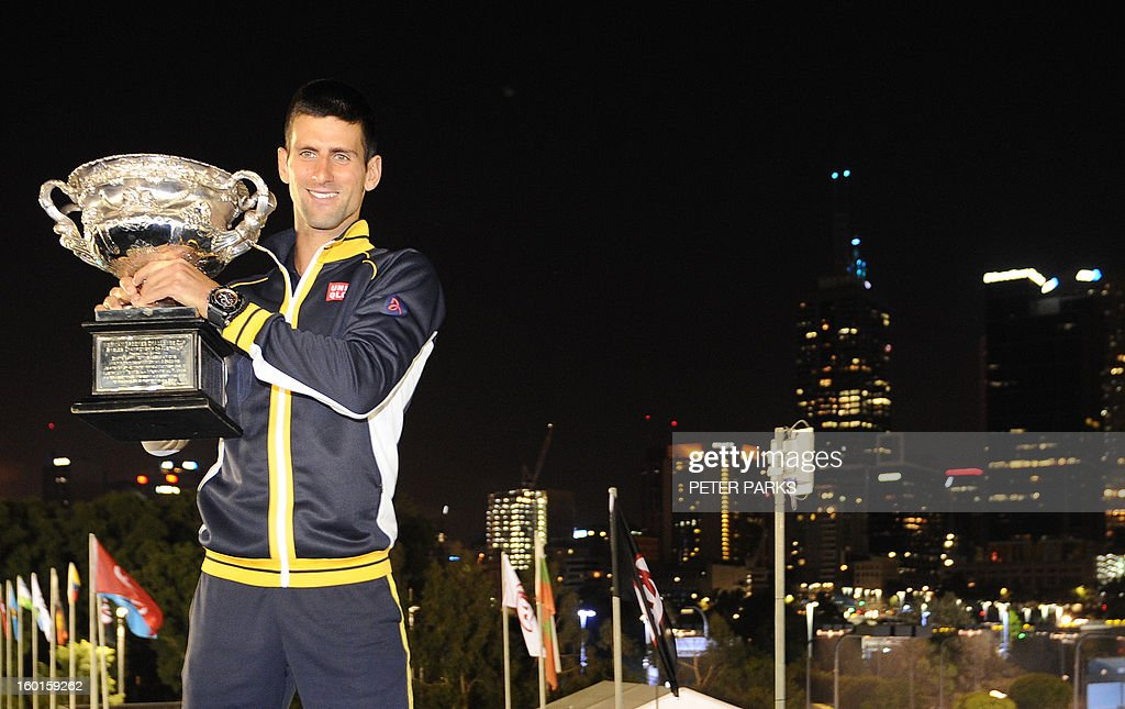 Serbia's Novak Djokovic for photographers during a presentation ceremony after his victory against Britain's Andy Murray in the men's singles final on day 14 of the Australian Open tennis tournament in Melbourne early on January 28, 2013.