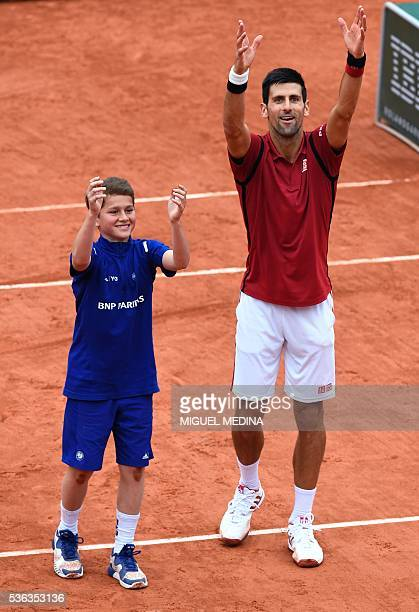 Serbia's Novak Djokovic gestures next to a ball boy after showing him how he celebrates after winning a match after winning his men's fourth round...