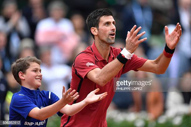Serbia's Novak Djokovic gestures with a ball boy as he celebrates after winning his men's fourth round match against Spain's Roberto Bautista at the...