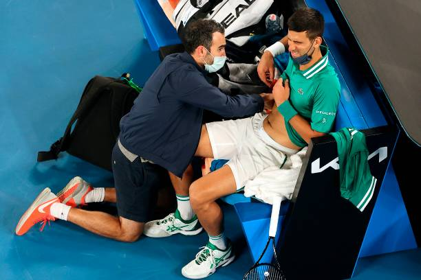 Serbia's Novak Djokovic gets medical treatment while playing against Taylor Fritz of the US during their men's singles match on day five of the...