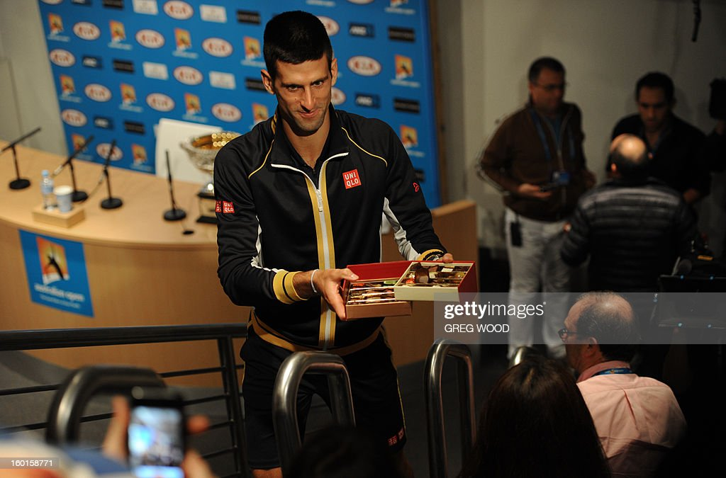 Serbia's Novak Djokovic hands out chocloates to journalists during a press conference after victory in his men's singles final against Britain's Andy Murray on day fourteen of the Australian Open tennis tournament in Melbourne early on January 28, 2013.