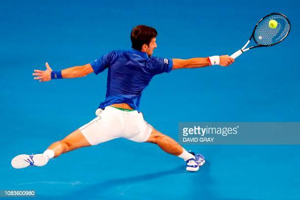 TOPSHOT Serbia's Novak Djokovic hits a return against France's JoWilfried Tsonga during their men's singles match on day four of the Australian Open...
