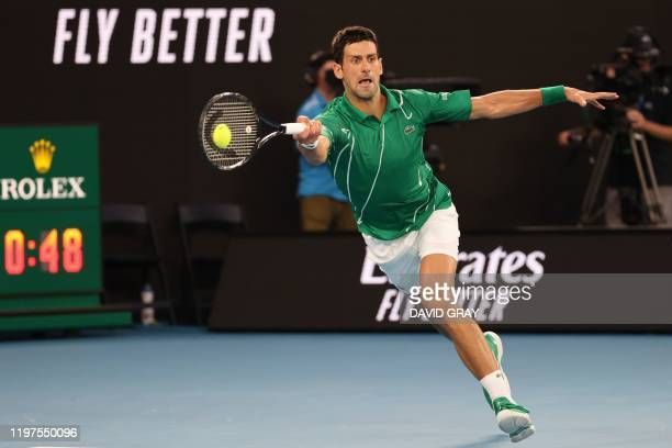 Serbia's Novak Djokovic hits a return against Switzerland's Roger Federer during their men's singles semi-final match on day eleven of the Australian...