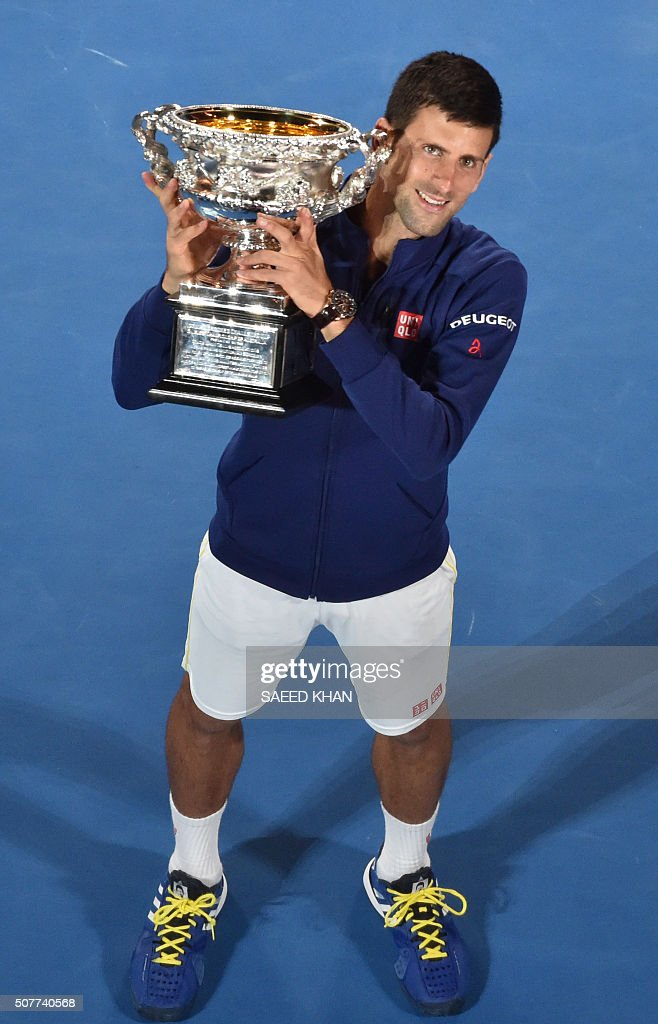 Serbia's Novak Djokovic holds The Norman Brookes Trophy as he celebrates after victory in his men's singles final match against Britain's Andy Murray on day fourteen of the 2016 Australian Open tennis tournament in Melbourne on January 31, 2016.