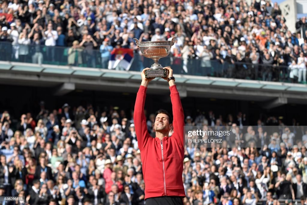 TOPSHOT - Serbia's Novak Djokovic holds the trophy after winning the men's final match against Britain's Andy Murray at the Roland Garros 2016 French Tennis Open in Paris on June 5, 2016. /