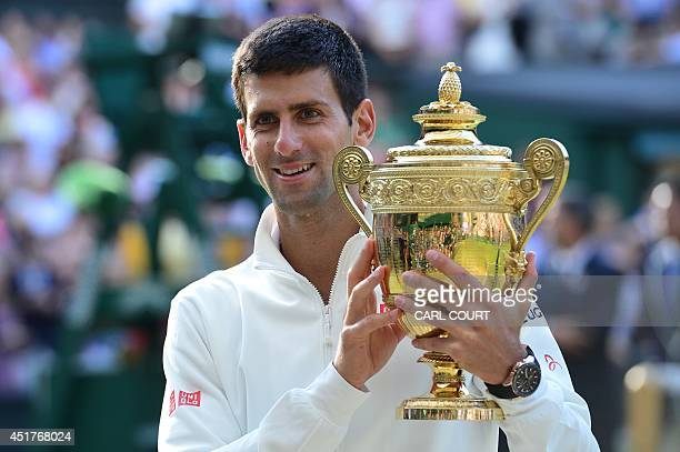 Serbia's Novak Djokovic holds the winner's trophy after beating Switzerland's Roger Federer in the men's singles final match during the presentation...