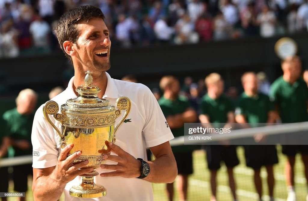 Serbia's Novak Djokovic holds the winners trophy after beating South Africa's Kevin Anderson 6-2, 6-2, 7-6 in their men's singles final match on the thirteenth day of the 2018 Wimbledon Championships at The All England Lawn Tennis Club in Wimbledon, southwest London, on July 15, 2018. (Photo by Glyn KIRK / AFP) / RESTRICTED