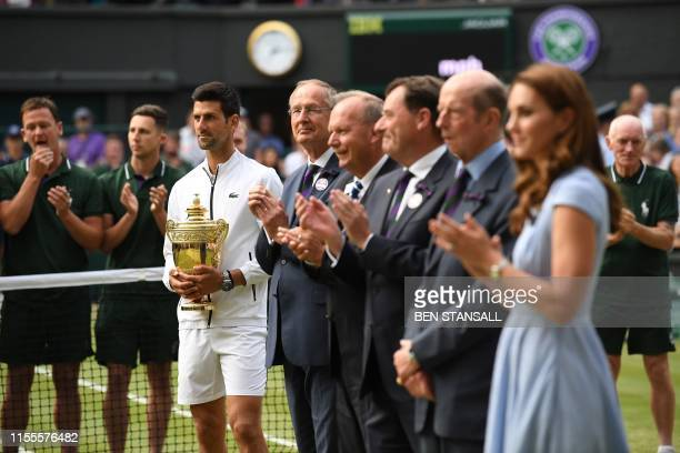 Serbia's Novak Djokovic holds the winner's trophy during the presentation after beating Switzerland's Roger Federer during their men's singles final...