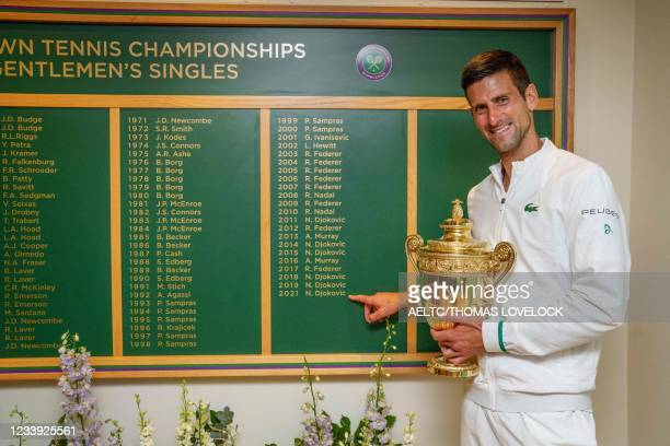 Serbia's Novak Djokovic holds the winner's trophy in front of the honours board and points to his name after defeating Italy's Matteo Berrettini...