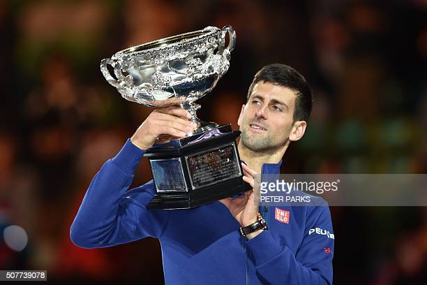 Serbia's Novak Djokovic holds up The Norman Brookes Challenge Cup after his victory during the men's singles final against Britain's Andy Murray on...