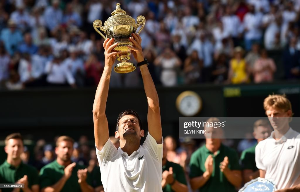 TOPSHOT - Serbia's Novak Djokovic holds up the winners trophy after beating South Africa's Kevin Anderson 6-2, 6-2, 7-6 in their men's singles final match on the thirteenth day of the 2018 Wimbledon Championships at The All England Lawn Tennis Club in Wimbledon, southwest London, on July 15, 2018. (Photo by Glyn KIRK / AFP) / RESTRICTED