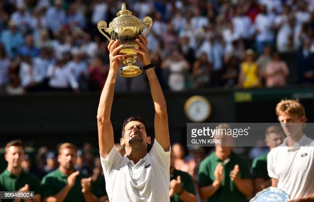 TOPSHOT Serbia's Novak Djokovic holds up the winners trophy after beating South Africa's Kevin Anderson 62 62 76 in their men's singles final match...