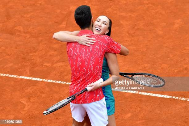 Serbia's Novak Djokovic hugs Jelena Jankovic during a tennis doubles against Serbia's Nenad Zimonjic and Olga Danilovic during a charity exhibition...