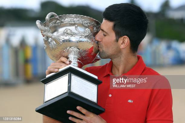 Serbia's Novak Djokovic kisses the Norman Brookes Challenge Cup trophy during a photo shoot in Melbourne on February 22 a day after his victory over...