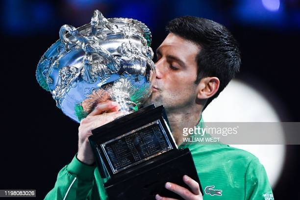 Serbia's Novak Djokovic kisses the Norman Brooks Challenge Cup trophy following his victory against Austria's Dominic Thiem in their men's singles...