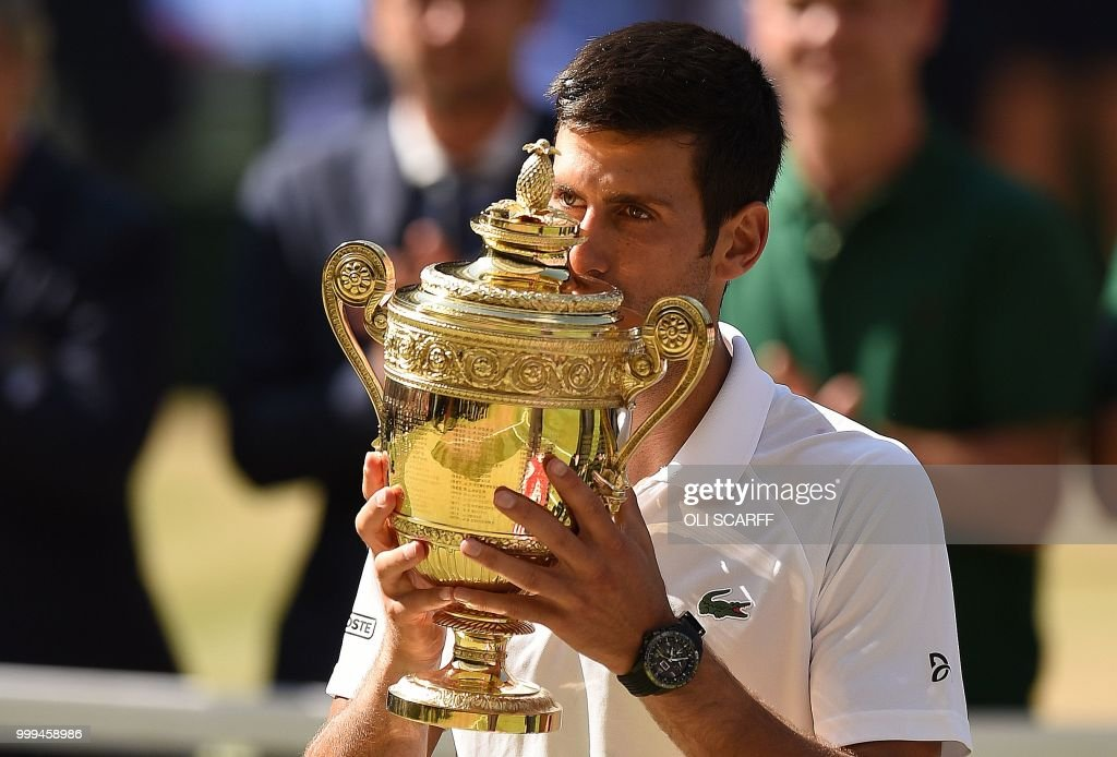 TOPSHOT - Serbia's Novak Djokovic kisses the winners the trophy after beating South Africa's Kevin Anderson 6-2, 6-2, 7-6 in their men's singles final match on the thirteenth day of the 2018 Wimbledon Championships at The All England Lawn Tennis Club in Wimbledon, southwest London, on July 15, 2018. (Photo by Oli SCARFF / AFP) / RESTRICTED