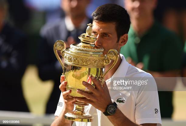 TOPSHOT Serbia's Novak Djokovic kisses the winners the trophy after beating South Africa's Kevin Anderson 62 62 76 in their men's singles final match...