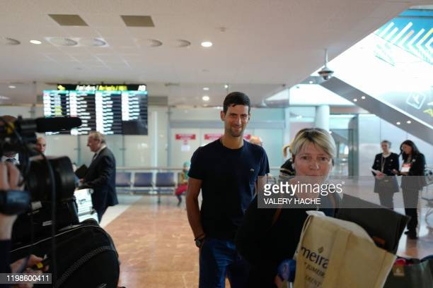Serbia's Novak Djokovic looks on as he arrives at Nice's airport southern France on February 4 two days after winning the men's singles final match...