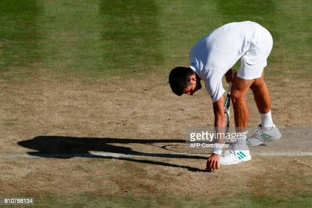 Serbia's Novak Djokovic picks up a piece of loose turf from the court after a point against Latvia's Ernests Gulbis during their men's singles third...