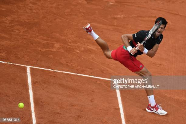 Serbia's Novak Djokovic plays a backhand return to Italy's Marco Cecchinato during their men's singles quarter-final match on day ten of The Roland...