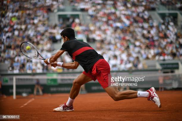 Serbia's Novak Djokovic plays a backhand return to Italy's Marco Cecchinato during their men's singles quarterfinal match on day ten of The Roland...