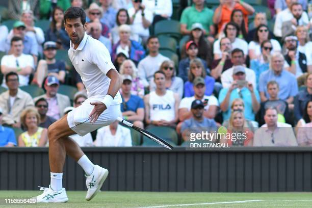 Serbia's Novak Djokovic plays a return behind his back against US player Denis Kudla during their men's singles second round match on the third day...