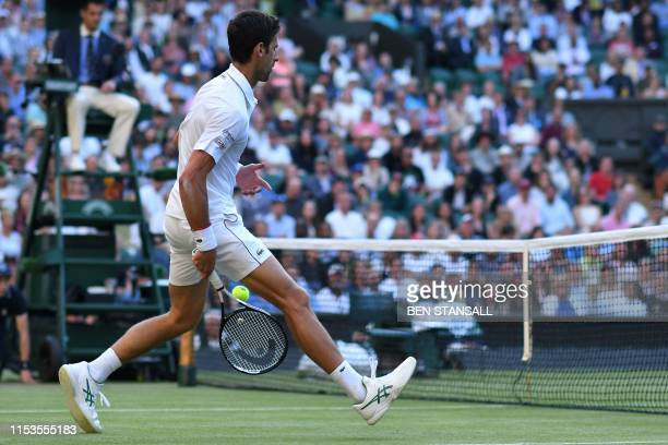 Serbia's Novak Djokovic plays a shot at the net through his legs against US player Denis Kudla during their men's singles second round match on the...