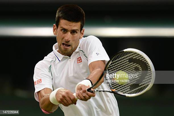 Serbia's Novak Djokovic plays a shot during his second round men's singles match against US player Ryan Harrison on day three of the 2012 Wimbledon...