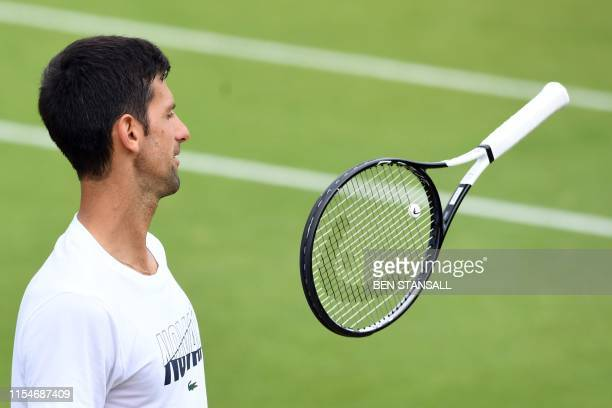 Serbia's Novak Djokovic plays with his racquet during a training session on day eight of the 2019 Wimbledon Championships at The All England Lawn...