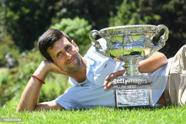 Serbia's Novak Djokovic poses for photographs with the championship trophy at the Royal Botanical Gardens in Melbourne on January 28 a day after his...