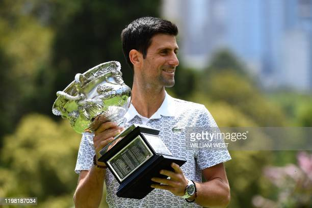 Serbia's Novak Djokovic poses for photographs with the Norman Brookes Challenge Cup trophy at the Royal Botanical Gardens in Melbourne on February 3...