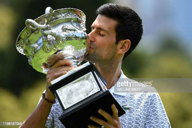 TOPSHOT Serbia's Novak Djokovic poses for photographs with the Norman Brookes Challenge Cup trophy at the Royal Botanical Gardens in Melbourne on...