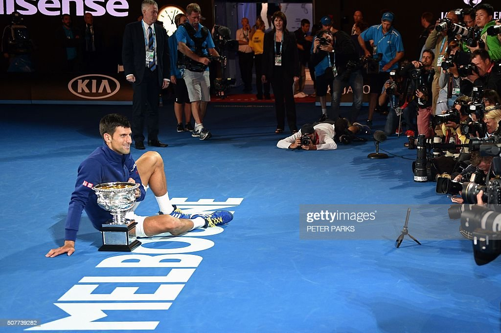 Serbia's Novak Djokovic poses for photographs with The Norman Brookes Challenge Cup after his victory during the men's singles final against Britain's Andy Murray on day 14 of the 2016 Australian Open tennis tournament in Melbourne on January 31, 2016.