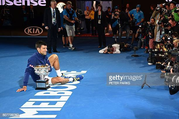 Serbia's Novak Djokovic poses for photographs with The Norman Brookes Challenge Cup after his victory during the men's singles final against...