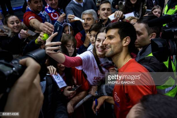 Serbia's Novak Djokovic poses for selfies with fans after Serbia's victory in the Davis Cup World Group first round against Russia at Cair sports...
