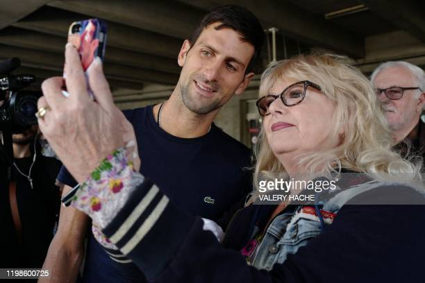 Serbia's Novak Djokovic poses with fans as he arrives at Nice's airport southern France on February 4 two days after winning the men's singles final...