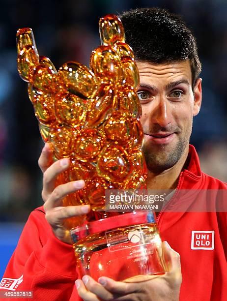 Serbia's Novak Djokovic poses with his trophy after winning of the Mubadala World Tennis Championship in Abu Dhabi againts Spain's David Ferrer, on...