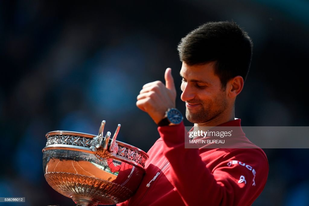 TOPSHOT - Serbia's Novak Djokovic poses with his trophy after winning the men's final match against Britain's Andy Murray at the Roland Garros 2016 French Tennis Open in Paris on June 5, 2016. /