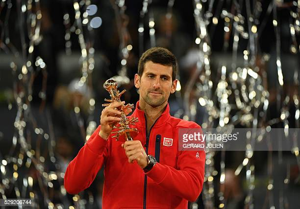 Serbia's Novak Djokovic poses with his trophy as he celebrates his victory over Britain's Andy Murray after the Madrid Open men's tennis final at the...