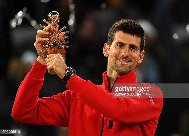 Serbia's Novak Djokovic poses with his trophy as he celebrates his victory over Britain's Andy Murray during the Madrid Open men's tennis final at...