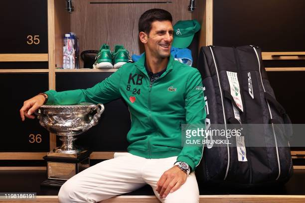 Serbia's Novak Djokovic poses with the Norman Brookes Challenge Cup in the locker room after winning the men's singles final match against Dominic...