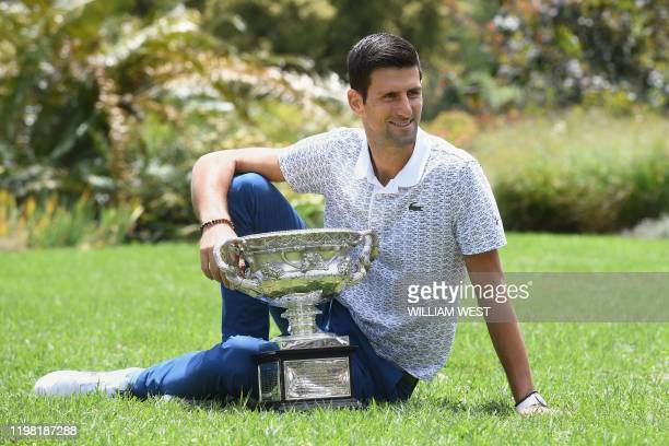 Serbia's Novak Djokovic poses with the Norman Brookes Challenge Cup trophy during a photo shoot in the Royal Botanical Gardens in Melbourne on...