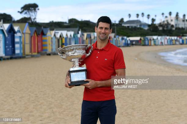 Serbia's Novak Djokovic poses with the Norman Brookes Challenge Cup trophy during a photo shoot in Melbourne on February 22 a day after his victory...