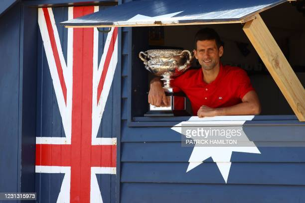 Serbia's Novak Djokovic poses with the Norman Brookes Challenge Cup trophy during a photo shoot at the Brighton Beach in Melbourne on February 22 a...