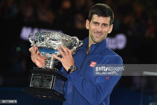TOPSHOT Serbia's Novak Djokovic poses with The Norman Brookes Trophy after victory in his men's singles final match against Britain's Andy Murray on...