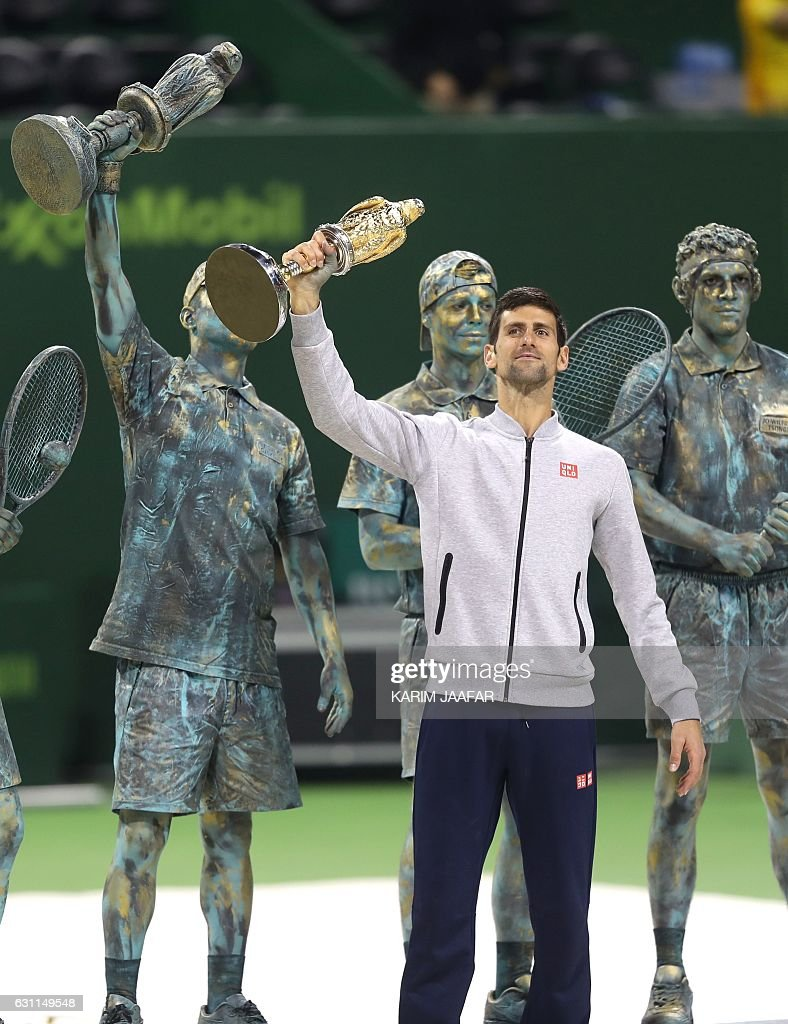 Serbia's Novak Djokovic poses with the winner's trophy after beating Britain's Andy Murray during their final tennis match at the ATP Qatar Open in Doha on January 7, 2017. / AFP / KARIM