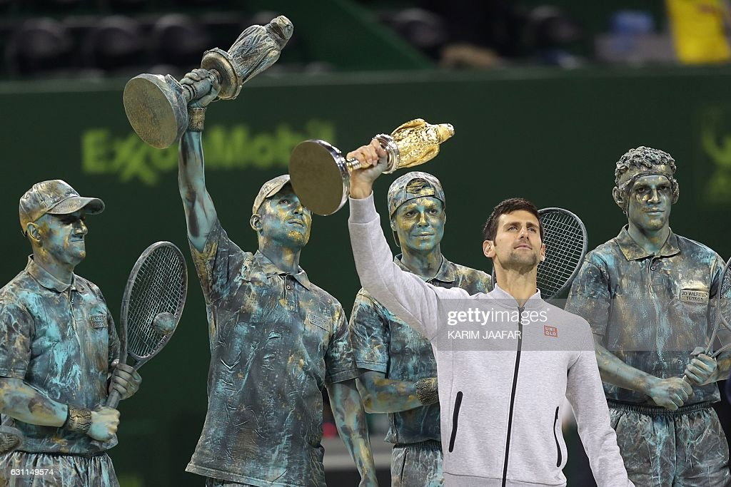 TOPSHOT - Serbia's Novak Djokovic poses with the winner's trophy after beating Britain's Andy Murray during their final tennis match at the ATP Qatar Open in Doha on January 7, 2017. / AFP / KARIM